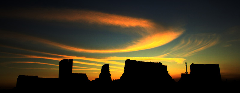Main image: Sunset illuminates wispy clouds over the remains of a major ancient building complex known as the 'Barracks' in January, 2010.